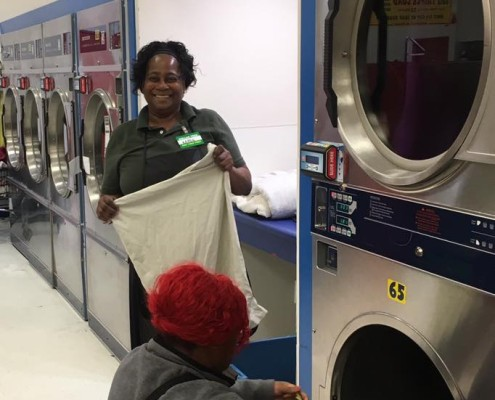 Happy volunteer at the free laundry event sponsored by to Laundry Love QC at Laudromania Davenport