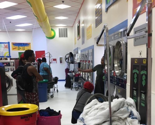 Instructions at free laundry event sponsored by to Laundry Love QC at Laudromania Davenport
