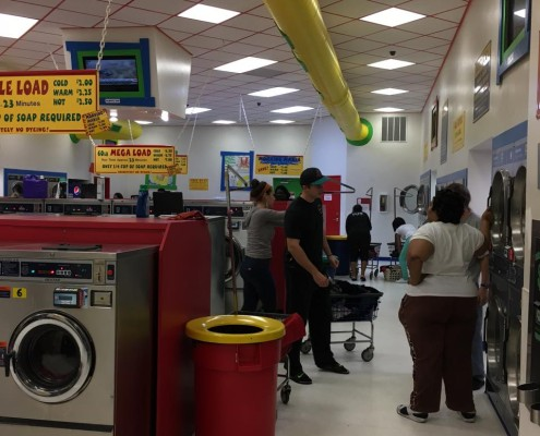 People using the dryers at the free laundry event sponsored by to Laundry Love QC at Laudromania Davenport