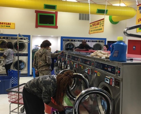People using the front load washing machines at the free laundry event sponsored by to Laundry Love QC at Laudromania Davenport