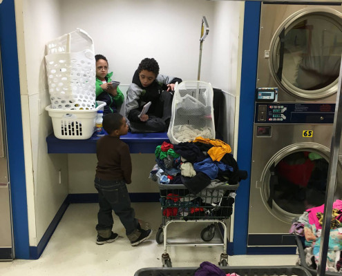 Children playing as the adults do laundry at Laundromania in Davenport, Iowa