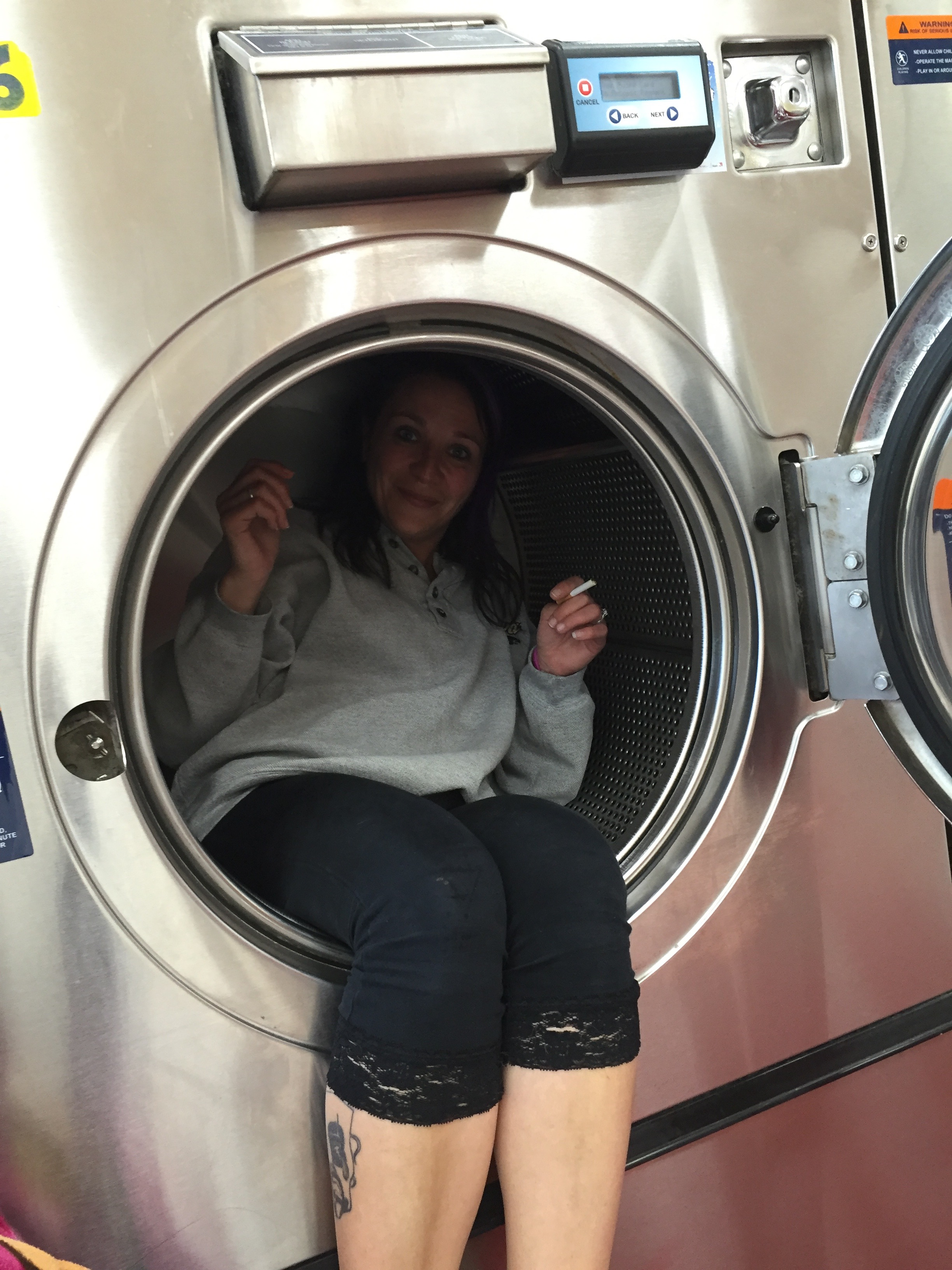 Women sitting inside a front load washing machine smoking