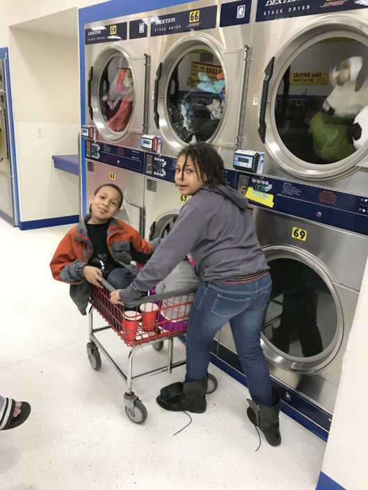 Kids having fun by the dryers at the Laundry Love QC event at Laundromania in Davenport, Iowa