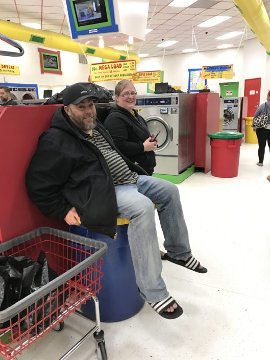 Man sitting on a garbage can at Laundry Love QC event at Laundromania in Davenport, Iowa