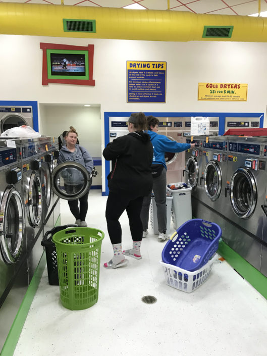 People doing laundry at Laundry Love QC event at Laundromania in Davenport, Iowa