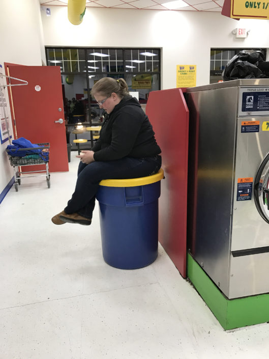 Women sitting on the garbage can at Laundry Love QC event at Laundromania in Davenport, Iowa