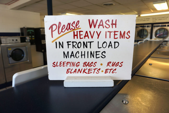 Please wash heavy items in front load machines sign inside Coralville Laundromania 24 hour Laundromat
