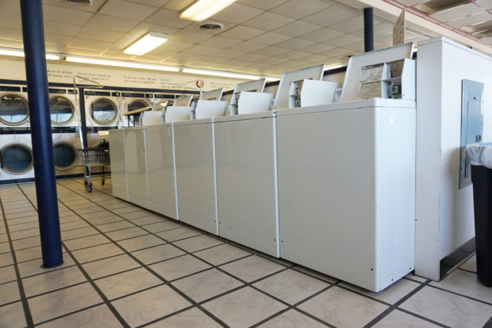 Row of 18lb Top Load washing machines inside Coralville Laundromania 24 hour Laundromat