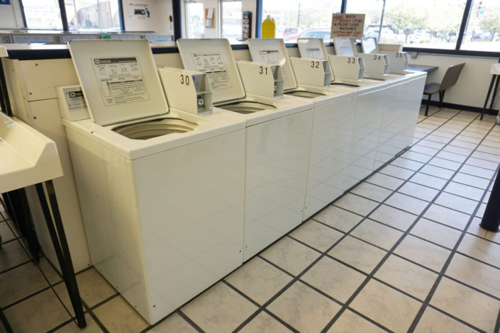 Row of 18lb top load washing machines inside Laundromania Coralville 24 hour Laundromat