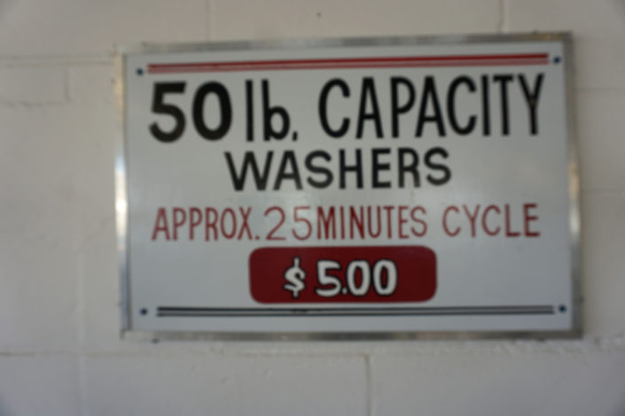 Sign 50lb capacity washers approx 25 minutes cycle $5.00