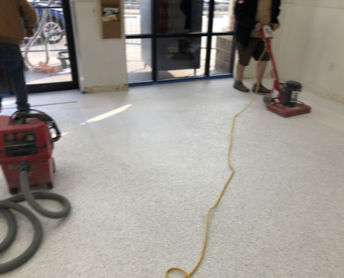 Sanding of the new flooring is installed at the Davenport Laundromania laundromat location